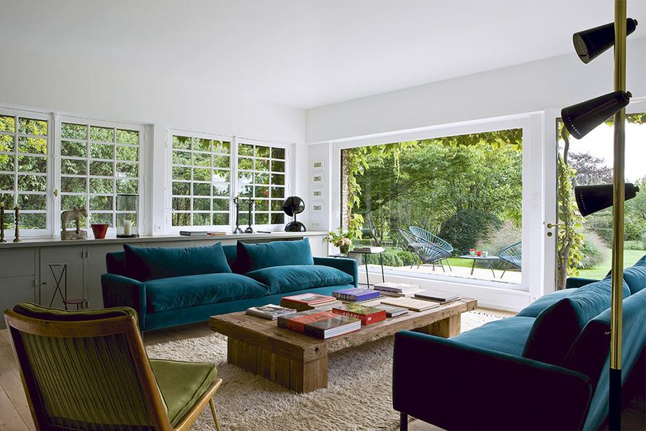 Главная гостиная получала продолжение в виде террасы. Глубокие диваны обтянуты переливчатым сине-зеленым бархатом, Caravane. В тон ему подобраны садовые кресла Acapulco, Sentou, — реплики мексиканской мебели 1950-х годов. Стол, Sempre. Деревянное кресло с бархатными подушками и торшер — винтаж. На полке у окна — оригинальный светильник работы Гае Ауленти. Еще одна деталь в духе 1950-х — встроенные шкафы — позволила эффективно использовать пространство под подоконником.