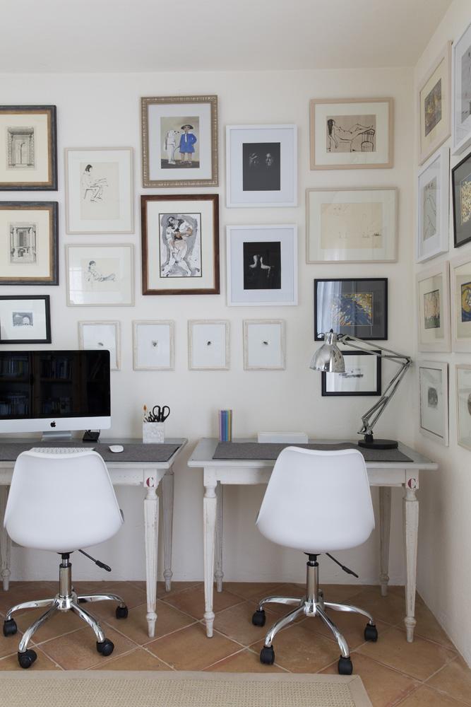 Кабинет на первом этаже. У старых кухонных столов поставлены современные офисные стулья. На стене — коллекция графики и фотографии.