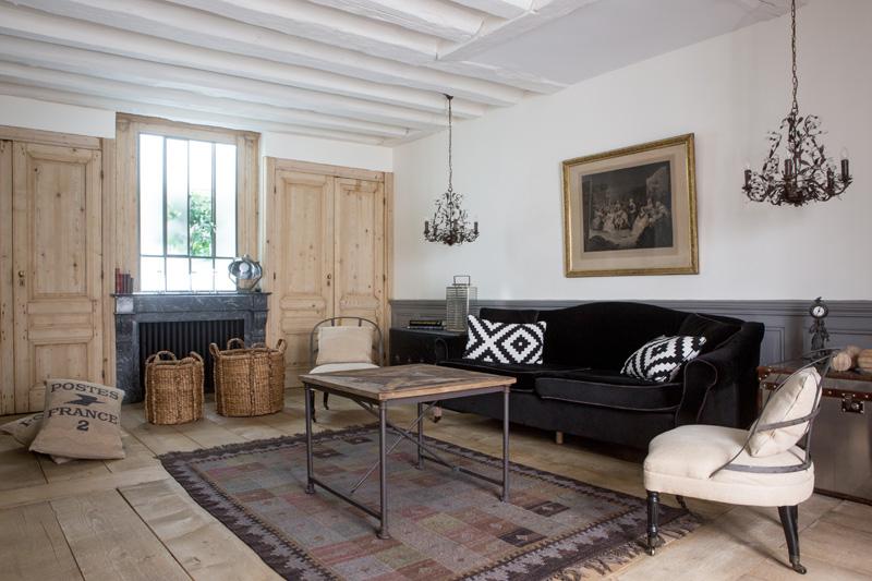 Гостиная. По бокам дивана, обитого черным бархатом, — антикварные дорожные сундуки. За некрашеными сосновыми дверями по обеим сторонам камина скрываются встроенные шкафы. Вся мебель куплена на блошиных рынках.
