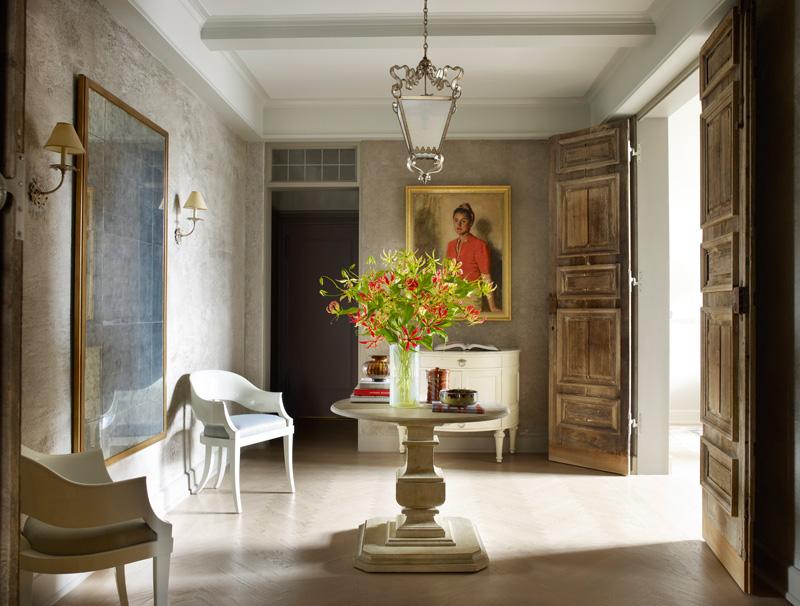 Холл в квартире Болтонов на Манхэттене. Стол с круглой столешницей — Dennis & Leen. Белые стулья, Saladino Furniture. На стенах, покрытых искусственно состаренной штукатуркой, — автопортрет художницы Эллен Эммет Ранд.