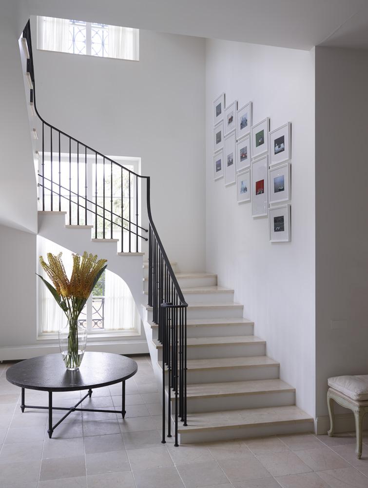 Лестничный холл. Стол с мраморной столешницей, Baker. Перила и стойки из металла изготовлены по эскизам дизайнера в мастерской «Сварог-Арт». Пол выложен травертином.