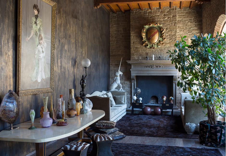 Гостиная. Старинный камин сохранился со времен постройки дома. Стена слева от камина оклеена обоями, имитирующими художественную штукатурку. Мебель и аксессуары, Roberto Cavalli Home. На столе — коллекция винтажного стекла от Daum и Эмиля Галле*. На стене — работа Джованни Болдини «Мадам Юго с сыном Жаном».