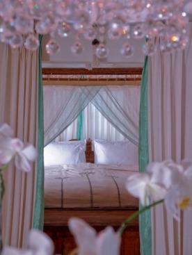 Фрагмент спальни в OAZIA Orchid. Эта вилла была оформлена первой и считается самой романтичной. Чтобы создать такую атмосферу, понадобилось много орхидей, много шелка и много хрусталя.