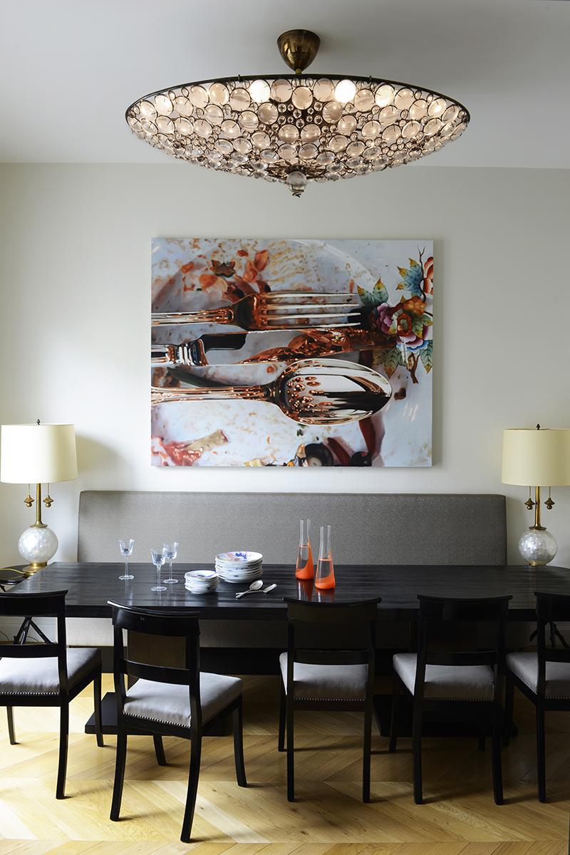 Cтоловая. Обеденную зону освещает необычная люстра, дизайн Марка Бразье-Джонса. На столе из шлифованной и покрытой лаком лиственницы, сделанном по эскизу Тициано Вудафьери, посуда, Muriel Grateau. На стене — работа индийского художника Субодха Гупты.
