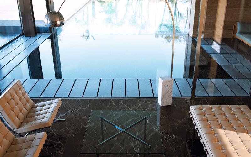 Фрагмент гостиной. Бассейн визуально объединяет интерьер с пространством за окном. Кресла и кушетка Barcelona, дизайн Людвига Мис ван дер Роэ, Knoll. Торшер Arco, дизайн Акилле и Пьера Джакомо Кастильони, Flos.