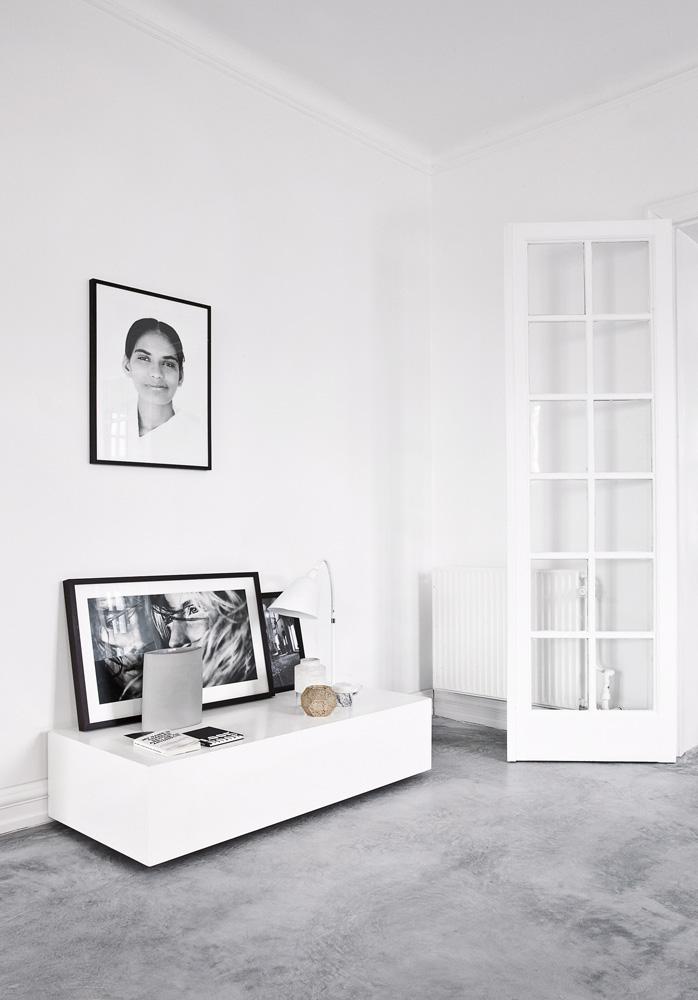 Гостиная. Cтены оштукатурены и выкрашены в белый цвет, полы — бетон. Напольный светильник на ножках Milk, похожий на крохотный табурет, спроектирован хозяином дома.