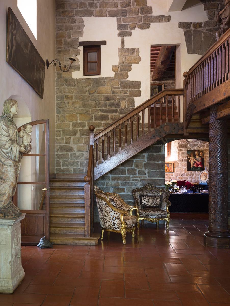 Старая лестница ведет на второй этаж, где находятся спальни. Полы выложены керамической плиткой. Кресла в «хищной» обивке, Roberto Cavalli Home.