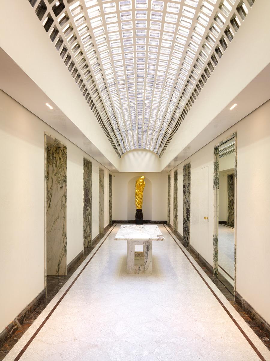 Зал «Променад». Цилиндрический свод потолка из бетона и стекла был построен еще в 1930 году архитектором Флорестано ди Фаусто и бережно отреставрирован Питером Марино. Пол выложен мрамором и стеклянной мозаикой. В нише — бронзовая скульптура, покрытая позолотой, автор Йохан Кретен, 2013 год.
