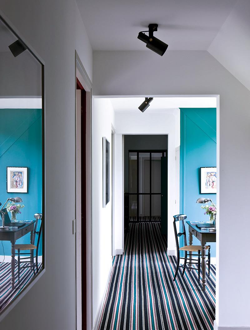 В угловом кабинете на первом этаже пол устлан паласом, дизайн Сары Лавуан для Hartley. Одна стена выкрашена в бирюзовый цвет — этот прием позволил по-новому зонировать пространство, не меняя его планировки.