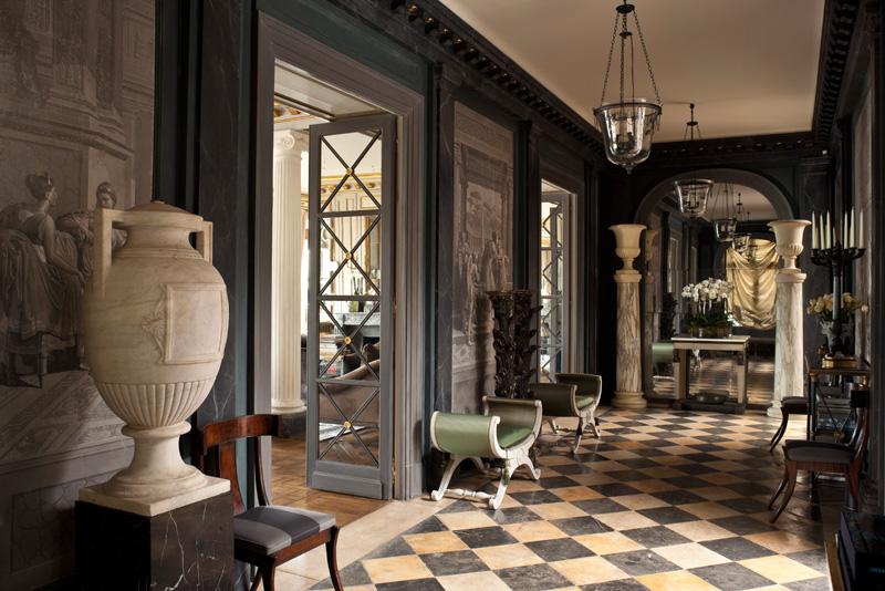Большая галерея квартиры. Двери слева ведут в гостиную. Как и стена в глубине холла, они облицованы старинными ртутными зеркалами. Роспись стен выполнена по мотивам гризайлей конца XVIII века. У стены слева — два шведских табурета XVIII века, обитых зеленым шелком. В глубине — две мраморные колонны, увенчанные вазами. Светильники изготовлены по старинным образцам из патинированной бронзы и дутого стекла.